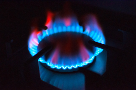 Gas burner burns with a blue and red flame in the dark. Gas stove. Energy for cooking, heating an apartment or house. Stock Photo