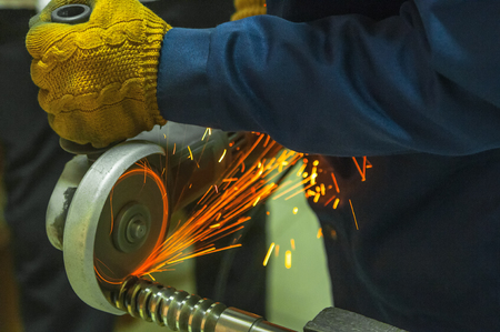 Worker cutting metal with old rotary angle grinder. Many red and yellow sparks while grinding iron. The hand in a dressing gown and glove holds the tool. Metal workpiece clamped in a vice.