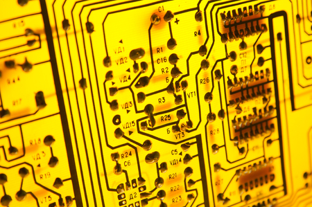 Yellow printed circuit board on the lighting. Soldering side of the PCB. Technological background with a circuit board texture. Selective focus.
