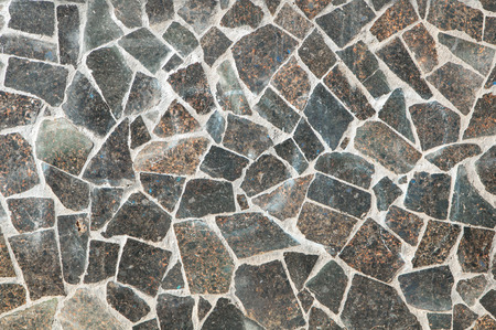 Mosaic wall granite pieces of building in sunny day. Pieces of marble bonded with gray cement. Stok Fotoğraf
