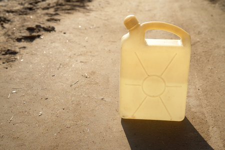 Plastic container with liquid on the road in a sunny day. Backlight.