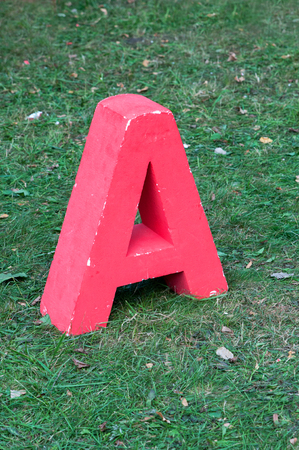 Red letter A stands in the grass Stock Photo