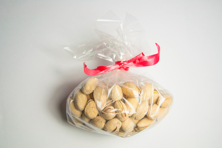 Unpeeled pistachios in a transparent gift box with a red bow Stock Photo