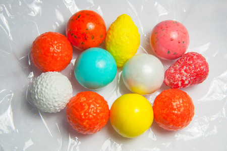 Multicolored gum balls chewing gums on transparent mica film. Delicious sweet round candy for children, hazardous to health. Stomach hazard.