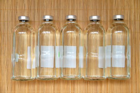 New medical bottles for infusions with physiologic saline on wood bamboo place mat texture background. Group of five bottles on the same level. Bottles  for saline IV drip dropper. View from above. 版權商用圖片