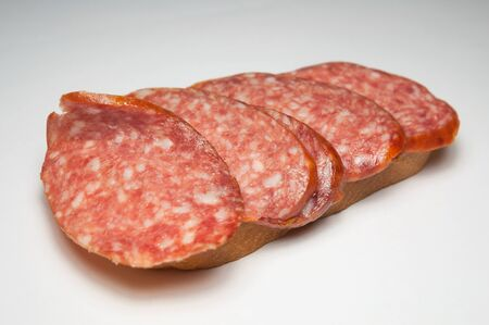 Red salami sandwich. Slices of red salami sausage and a loaf. Product for a snack at work. Sliced sausage hanging from a loaf. Banque d'images - 132070365