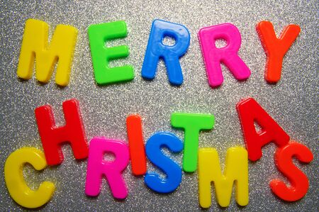 Merry cristmas. Written in a colorful plastic letters on a shiny silver background.  Inscription merry christmas from colour plastic letters. Letters for teaching children the English alphabet.