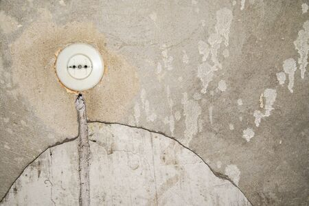 Old electrical outlet without grounding on the old gray wall. Round plastic wall socket on the plastered with cement wall. Copyspace for text. The concept of repairing old apartments.
