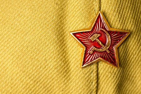 Old soviet military badge with hammer and sickle on light green cloth headgear. Red five-pointed soviet communist gold red star. Symbol of the USSR. Space for the text. Victory Day Concept. Banque d'images