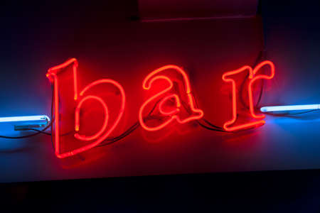 Red neon bar sign with blue neon lines on the sides, lower case letter lights. Concept of night life in city and place to relax after a hard week of work in the city.