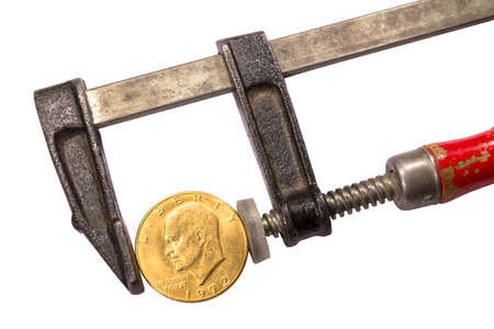 American gold coin fixed in an old clamp with a common red handle isolated on white background. Liberty under pressure.  Concept of problems in economics and financial crisis. Banco de Imagens