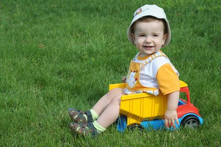 toy truck: a smiling baby with a pacifier is sitting in the toy truck on the grass