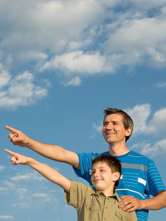 distant: dad and son are pointing a distant object while walking outdoors