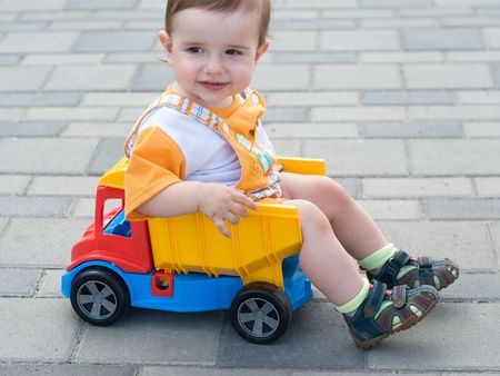 a smiling baby boy is sitting in the toy truck photo