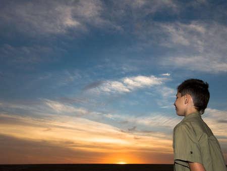 boy below the multicolored sky photo