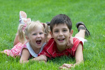 sandals: a smiling boy and a little girl are lying on the grass in the park