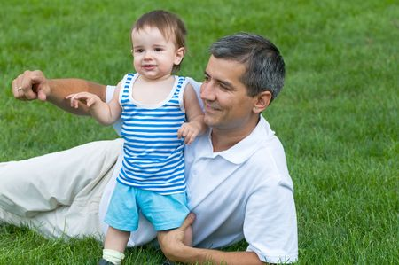 a father and his son are playing on the grass in the park Stock Photo - 5337757