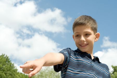 teen is pointing a distant object while walking outdoors photo