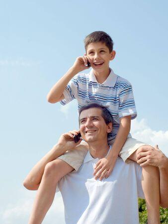 padres hablando con hijos: un padre y su hijo son loking adelante y que hablan m�s de los m�viles