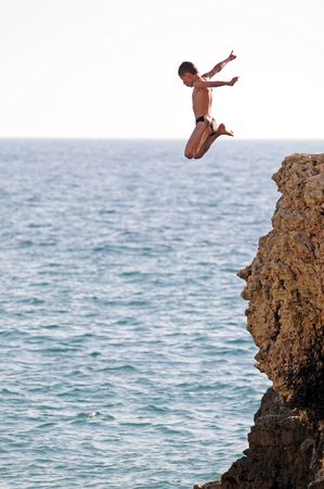 sky diving: an expressive boy is diving into the sea Stock Photo