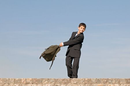 a happy pre-teen is coming back from school holding his schoolbag in his hands photo
