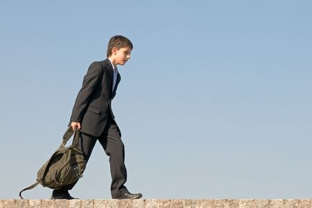 a successful school student is walking home holding his schoolbag in his hands photo