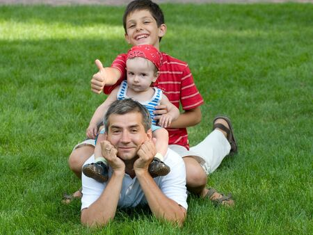 two sons are sitting on their fathers back holding thumbs up photo