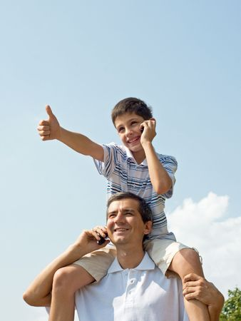 a father and his son are loking forward and speaking over mobiles photo