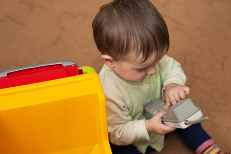 A little boy is playing with a telephone receiver photo