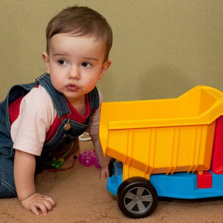 A little boy is playing with toy truck photo