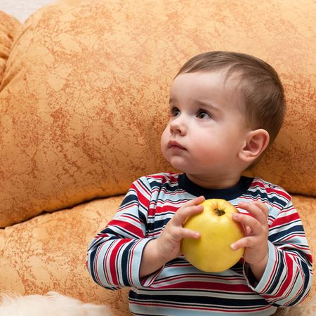 A thoughtful baby boy is sitting on the sofa and holding an apple in his hands Stock Photo - 6171157