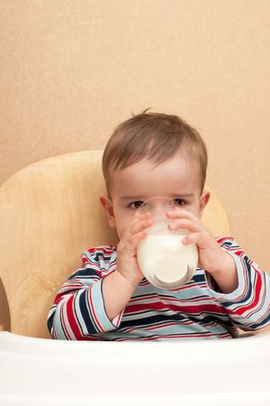 A toddler is drinking a glass of milk photo