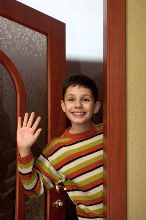 waving: A happy boy is leaving a room and waving farewell