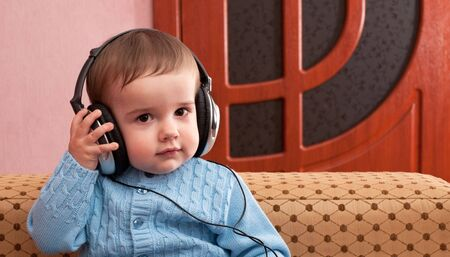 A portrait of a kid in blue holding headphones Stock Photo - 6296055