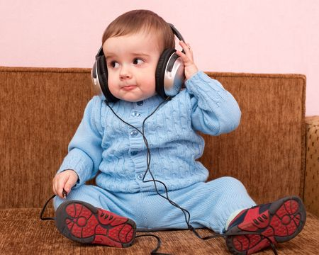 baby in suit: A kid in blue is sitting on the sofa playing with headphones Stock Photo