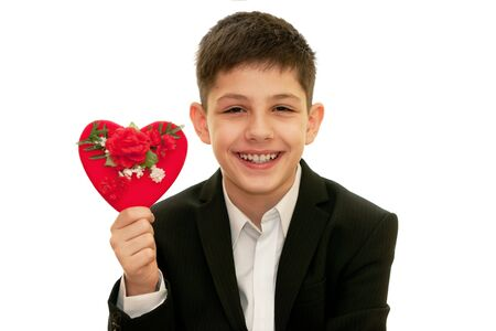 A smiling boy is showing a red heart with flowers on it; isolated on the white background photo