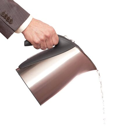 A man in a suit is holding a chrome kettle in his right hand and pouring water, isolated on white photo
