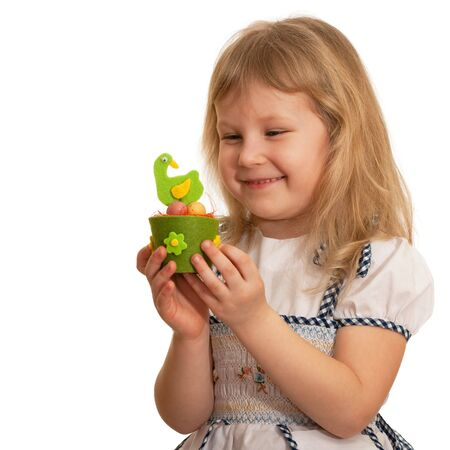 A smiling girl is holding an Easter toy; isolated on the white background photo