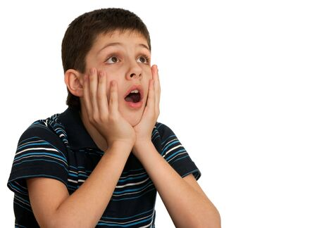 dissappointed: A shocked boy is holding his hands at his face; isolated on the white background Stock Photo