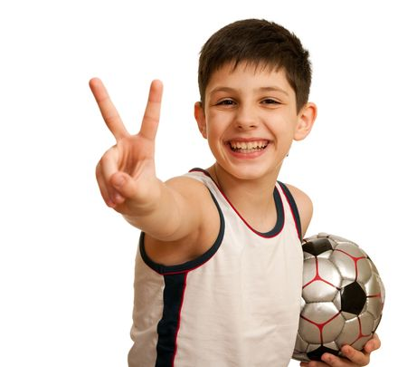 A happy kid is showing a victory sign with his right hand and holding a ball in his left hand; isolated on the white background photo