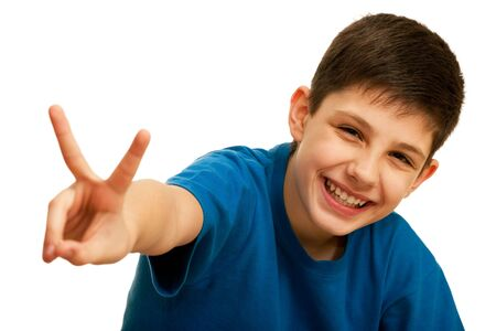 A portrait of a happy kid in blue showing a victory sign; isolated on the white background photo