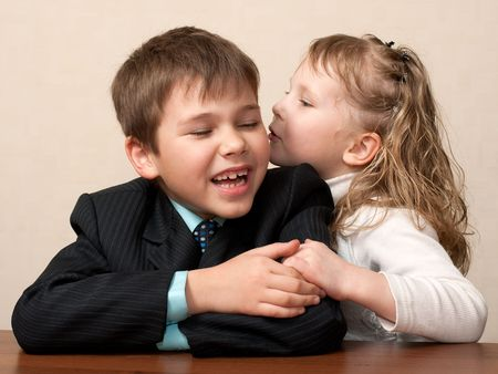 A girl is wispering to a boy sitting at the desk in the classroom photo