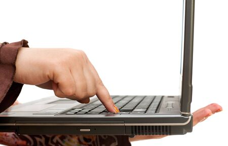 A woman hand is pushing a button on the laptop keyboard; isolated on the white background photo
