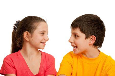ni�os hablando: Una ni�a sonriente est� escuchando a su amigo; aislado en el fondo blanco