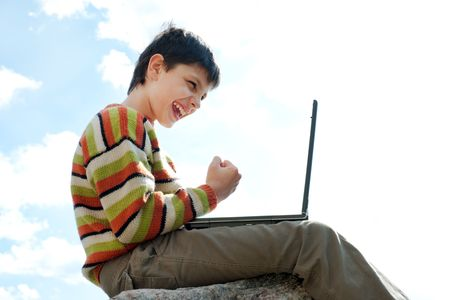 A shouting teen is sitting on the rock outside and playing a computer game photo