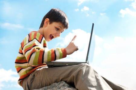 A handsome teen is pointing up while sitting on a stone and playing a game on the laptop photo