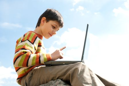 A handsome kid is studying holding a laptop on his knees in front of the blue sky photo