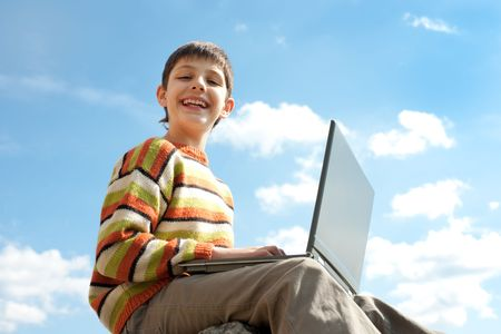 A happy teen is smiling holding a laptop on his knees in front of the blue sky photo