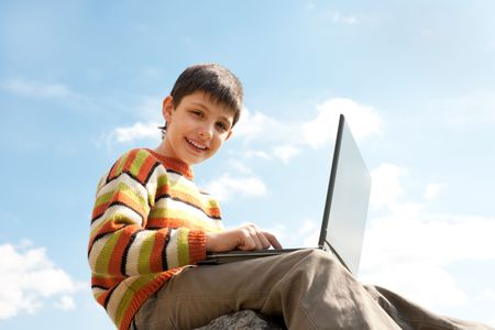 A happy kid is studying holding a laptop on his knees in front of the blue sky photo