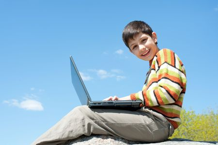 A happy boy is smiling holding a laptop on his knees in front of the blue sky photo